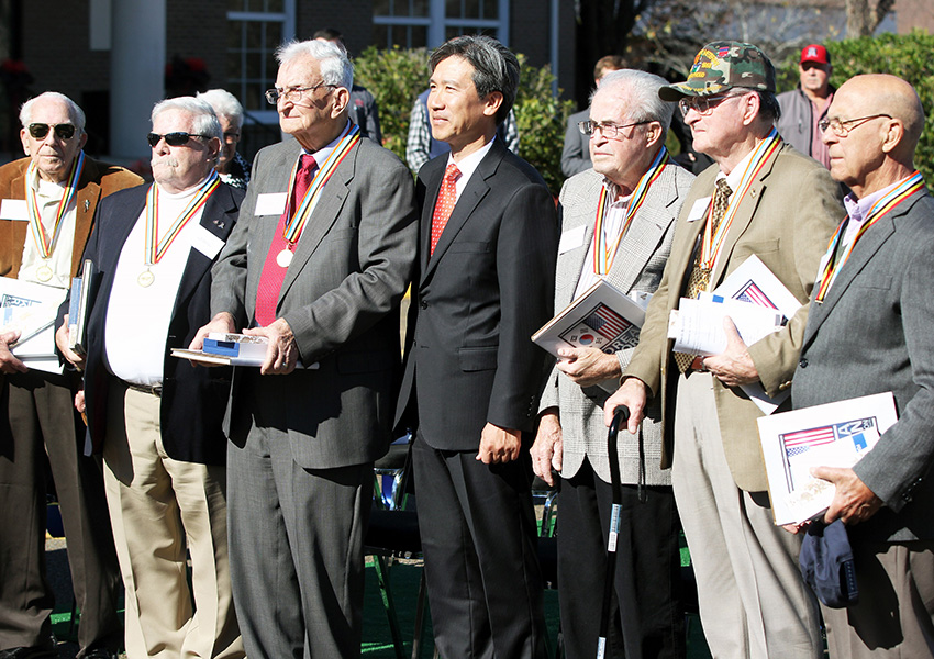 Republic of Korea Consul General Hyung Gil Kim, at center, with veterans he presented with the Ambassador for Peace Medal for their service to his country during the Korean War.