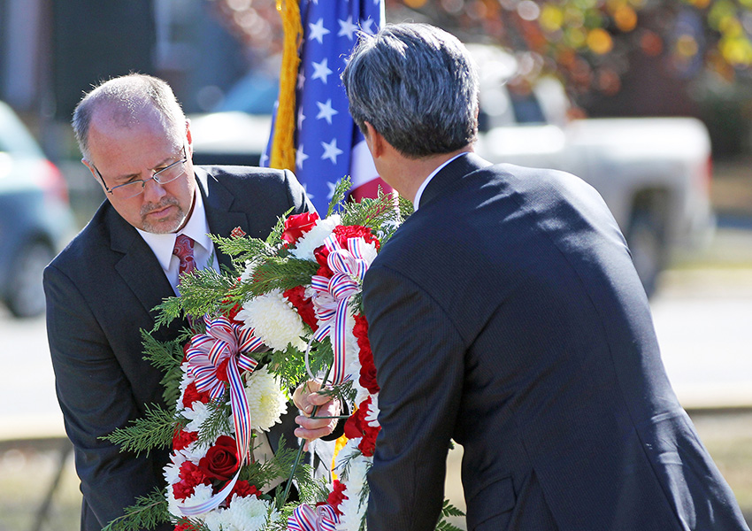 East Mississippi Community College President Dr. Thomas Huebner, at left, and Republic of Korea Consul General Hyung Gil Kim prepare to lay a wreath at the Korean War memorial on the college's campus.