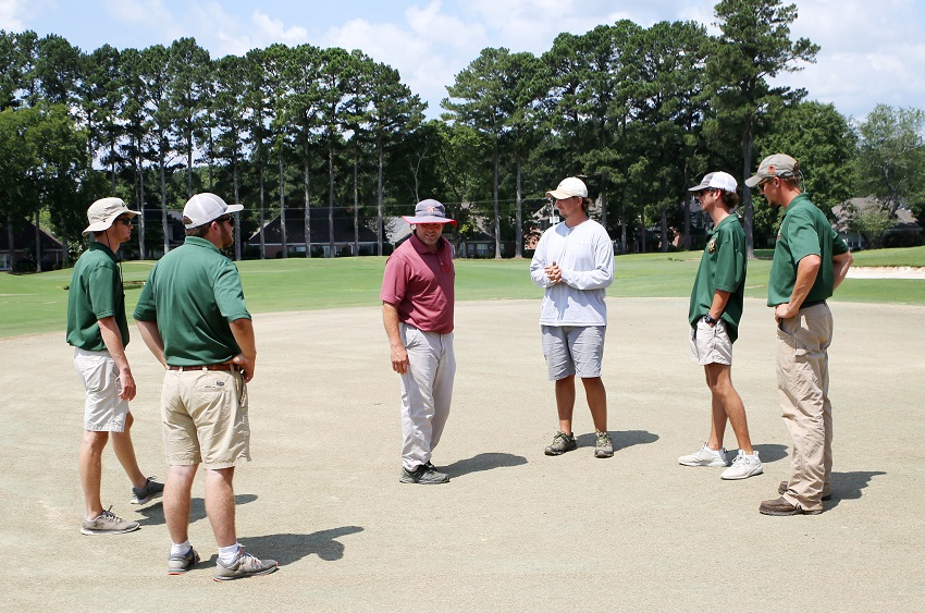East Mississippi Community College Director of Golf Will Arnett, at center, inspects the grass on one of the greens at the Lion Hills Center & Golf Club. The grass on holes 1-9 has been killed and work is under way to convert the greens to Tif-Eagle, a high quality grass intended to improve putting speed and consistency. Arnett is joined, from left, by EMCC Golf / Recreational Turf Management students Tanner Jacobs of Caledonia, Hunter Calhoun of Madison, Winn Kent of Greenville, and Blake Miller of Starkville. Golf course superintendent Derek Havard is at the far right.