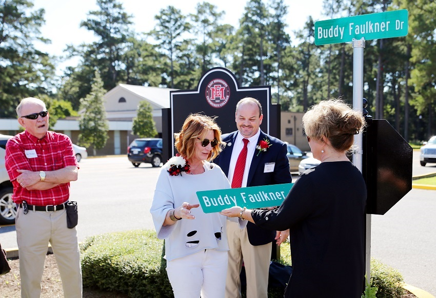 A road on East Mississippi Community College's Scooba campus has been named after the late Buddy Faulkner, an EMCC alumnus. Here, Faulkner's widow, Tina Faulkner, is presented with a duplicate road sign by EMCC Director of Alumni Affairs and Foundation Operations Gina Cotton.