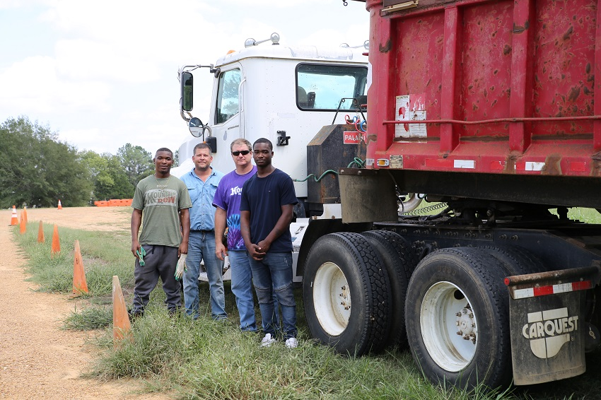 East Mississippi Community College's Commercial Truck Driving program student Ronald Gore of Columbus, Chris Lovelace of Webster County, program instructor Mark Dodson, and student Montavious Walker stand beside a dump truck donated by Phillips Contracting. Commercial Truck Driving will now include training on the use of construction equipment.