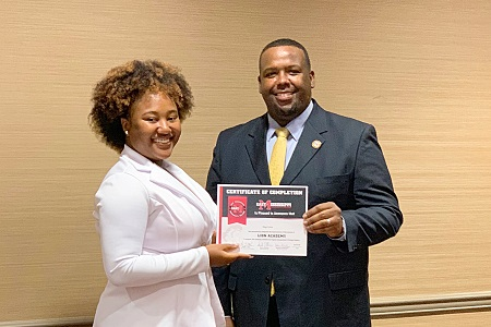 East Mississippi Community College Lion Academy graduate Sage Love, at left, is presented a certificate of completion by EMCC Associate Dean of Instruction James Rush.