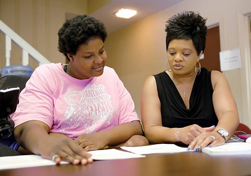 Macon resident Shaleta Odeneal, at left, goes over paperwork with East Mississippi Community College Macon Center Director Amanda Crawford. The EMCC Macon Center has expanded its program offerings and hours of operation.