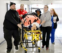 Students enrolled in all of East Mississippi Community College's Division of Nursing and Allied Health programs took part in a large-scale simulation in which a patient suffering a medical emergency was transported by paramedics and emergency medical technicians to the emergency room and sent to a catheterization lab before winding up in the operating room.