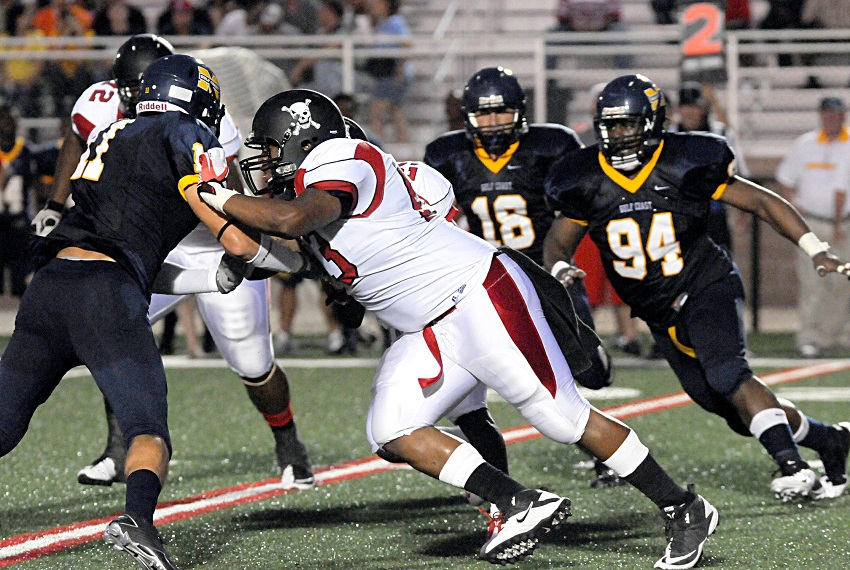 "Former Lions football standout Derrick ""DJ"" Wilson, center, holds off a Gulf Coast Community College defender in this file photo from the 2011 season in which the Lions were undefeated and claimed a national championship. Wilson now owns a food catering business."