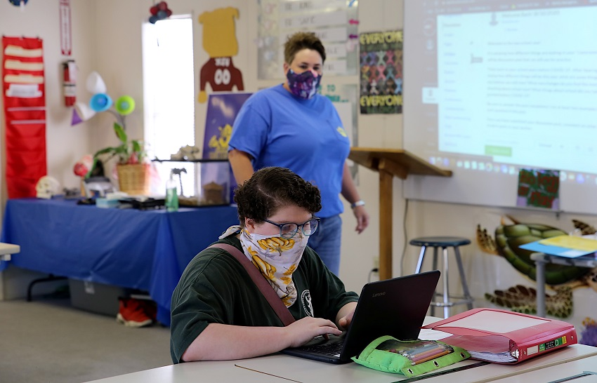 Golden Triangle Early College High School junior Sarah Clark works on an assignment while biology teacher Brandy Burnett, at back, looks on. The fall term at GTECHS began Aug. 10 and some students returned for in-class instruction while others are taking virtual classes online.