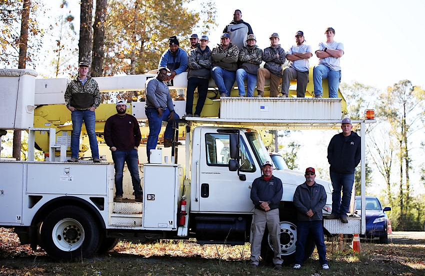 The Utility Lineworker Technology program is offered on East Mississippi Community College's Scooba campus. Here, students take a break from their studies for a photo. Standing on the ground, from left, are program instructors Chuck Cotton and Kevin Rushing.