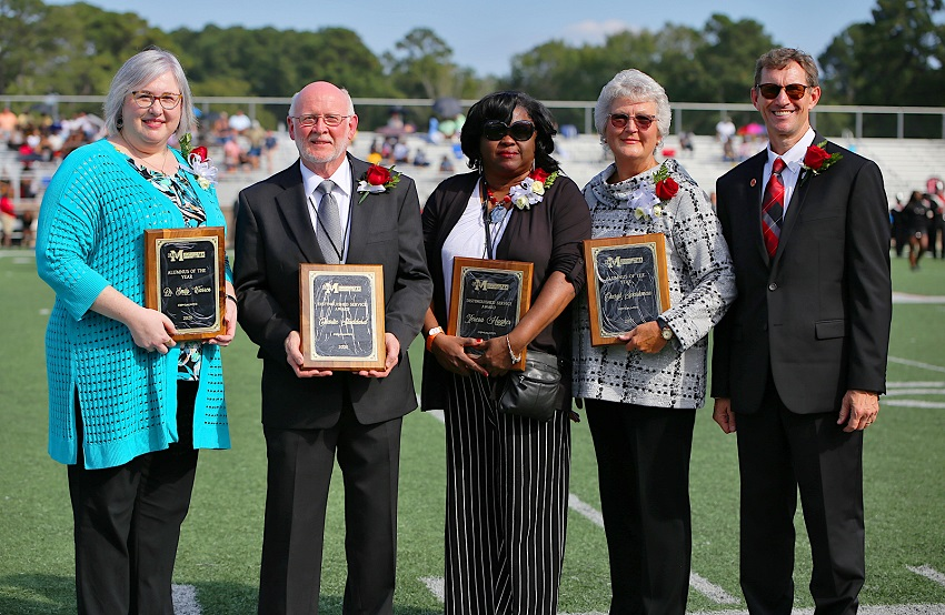 Four East Mississippi Community College alumni were honored Oct. 9 during the halftime of the college's Homecoming football game and were presented plaques by EMCC President Dr. Scott Alsobrooks, far right. The honorees are, from left, Dr. Emily Warren, 2020 Alumna of the Year; Charlie Studdard, 2020 Distinguished Service Award; Teresa Hughes, 2021 Distinguished Service Award, and Cheryl Sparkman, 2021 Alumna of the Year.