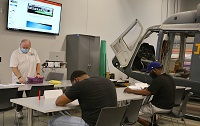 EMCC Workforce Trainer Carey Butler, at left, works with students in the Manufacturing Skills, Composite and Assembly course tailored to provide the skills needed by employees with Aurora Flight Sciences, a Boeing Company.