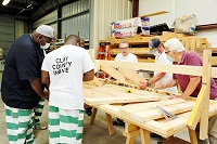 East Mississippi Community College Construction Skills instructor Johnny Duren, at right, watches as inmates from the Clay County Detention Center, who are enrolled in the program, frame a roof during class.